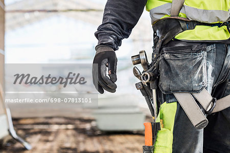 Midsection of worker wearing tool belt at construction site Stock Photo - Premium Royalty-Free, Image code: 698-07813101