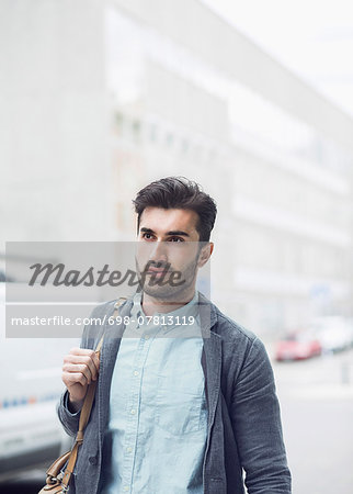 Young businessman looking away while walking on city street Stock Photo - Premium Royalty-Free, Image code: 698-07813119