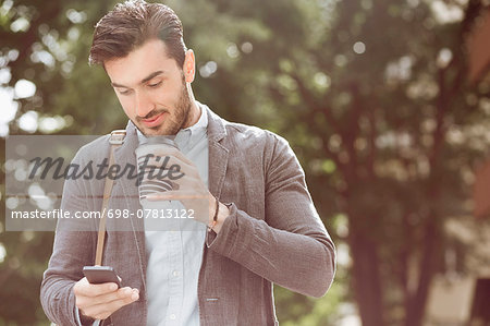 Young businessman having coffee while using smart phone outdoors Stock Photo - Premium Royalty-Free, Image code: 698-07813122