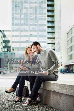 Business people discussing over digital tablet while sitting on seat in city Stock Photo - Premium Royalty-Free, Image code: 698-07813141