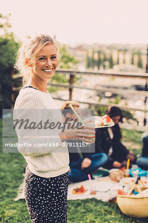 Side view portrait of happy woman holding breakfast at rooftop party Stock Photo - Premium Royalty-Free, Image code: 698-07813157