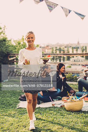 Portrait of happy woman with breakfast walking at rooftop party Stock Photo - Premium Royalty-Free, Image code: 698-07813158