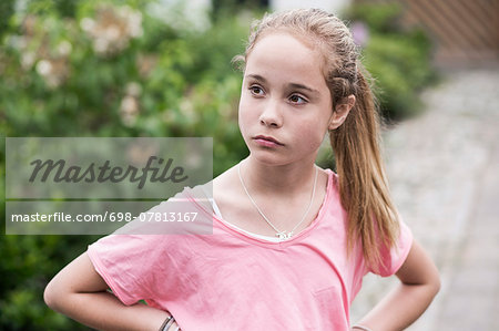 Angry girl with hands on hips looking away outdoors Stock Photo - Premium Royalty-Free, Image code: 698-07813167