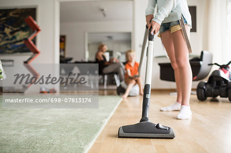 Low section of girl cleaning floor with vacuum cleaner at home Stock Photo - Premium Royalty-Free, Image code: 698-07813174