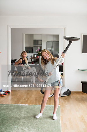 Full length portrait of playful girl holding vacuum cleaner at home with mother sitting in background Stock Photo - Premium Royalty-Free, Image code: 698-07813175
