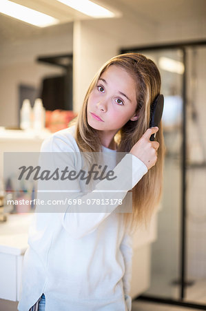 Girl combing hair at home Stock Photo - Premium Royalty-Free, Image code: 698-07813178