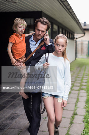 Businessman using mobile phone while walking with children at yard Stock Photo - Premium Royalty-Free, Image code: 698-07813183