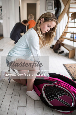 Girl packing badminton bag at home with family in background Stock Photo - Premium Royalty-Free, Image code: 698-07813188