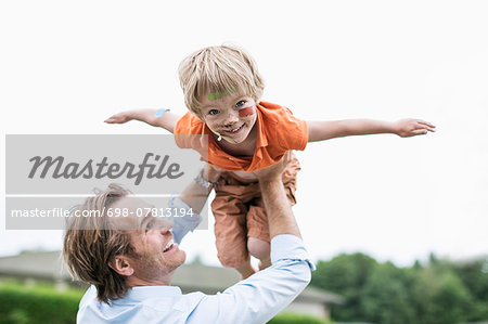 Playful father lifting injured son against clear sky Stock Photo - Premium Royalty-Free, Image code: 698-07813194