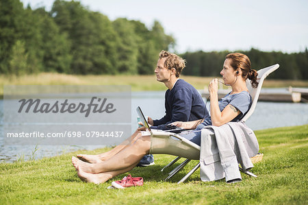 Full length side view of mature couple relaxing on desk chairs at lakeshore Stock Photo - Premium Royalty-Free, Image code: 698-07944437