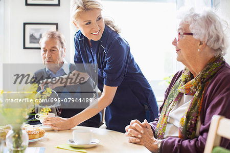 Happy female caretaker serving coffee to senior people at nursing home Stock Photo - Premium Royalty-Free, Image code: 698-07944489