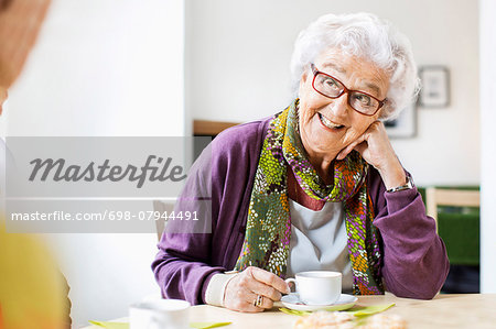 Happy senior woman looking at friend while having coffee at breakfast table in nursing home Stock Photo - Premium Royalty-Free, Image code: 698-07944491