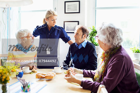 Female caretaker with senior people discussing at breakfast table in nursing home Stock Photo - Premium Royalty-Free, Image code: 698-07944492
