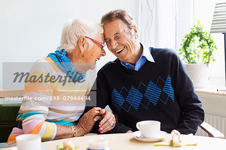 Loving senior couple laughing at nursing home Stock Photo - Premium Royalty-Free, Image code: 698-07944494