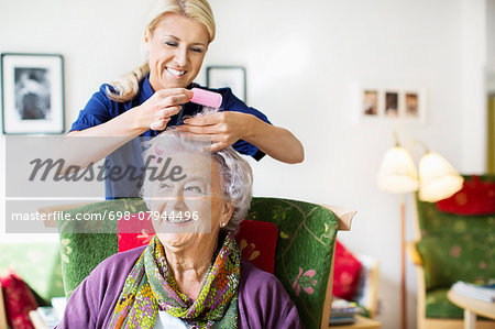 Happy female caretaker putting curlers to senior woman's hair at nursing home Stock Photo - Premium Royalty-Free, Image code: 698-07944496