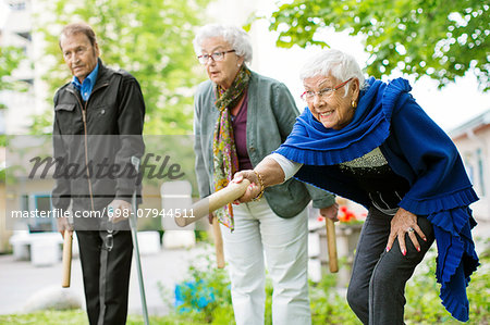 Happy senior people playing kubb game at park Stock Photo - Premium Royalty-Free, Image code: 698-07944511