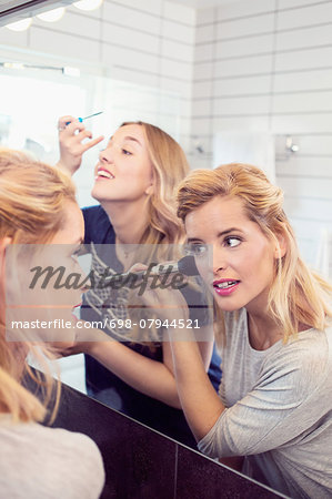 Young female friends applying makeup in mirror Stock Photo - Premium Royalty-Free, Image code: 698-07944521