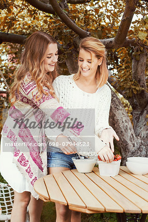 Happy sisters preparing smoothie at outdoors table Stock Photo - Premium Royalty-Free, Image code: 698-07944523