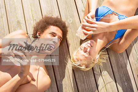 Man looking at woman using smartphone while lying on boardwalk Stock Photo - Premium Royalty-Free, Image code: 698-07944525