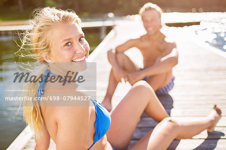 Portrait of smiling woman relaxing on boardwalk with man in background Stock Photo - Premium Royalty-Free, Image code: 698-07944527