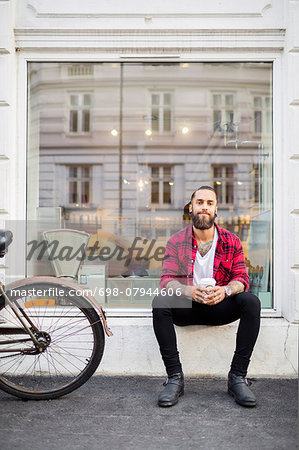 Portrait of smiling owner with coffee sitting outside candy store Stock Photo - Premium Royalty-Free, Image code: 698-07944606