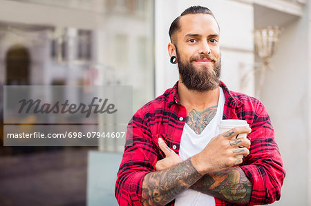 Portrait of smiling owner with coffee outside candy store Stock Photo - Premium Royalty-Free, Image code: 698-07944607