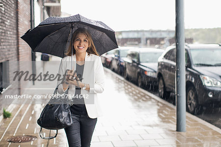 Portrait of smiling businesswoman walking on sidewalk with umbrella during rainy season Stock Photo - Premium Royalty-Free, Image code: 698-07944642