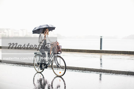 Full length of businesswoman riding bicycle on wet city street during rainy season Stock Photo - Premium Royalty-Free, Image code: 698-07944643