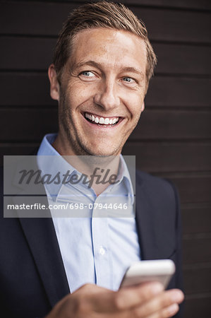 Happy businessman using smart phone Stock Photo - Premium Royalty-Free, Image code: 698-07944646