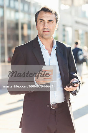 Businessman looking away while holding mobile phone and disposable coffee cup on city street Stock Photo - Premium Royalty-Free, Image code: 698-07944663