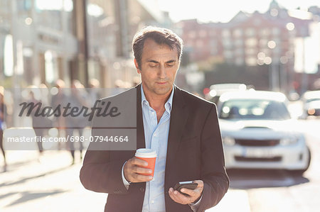 Businessman using mobile phone and holding disposable coffee cup while walking on city street Stock Photo - Premium Royalty-Free, Image code: 698-07944664