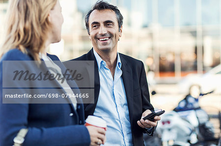 Happy businessman talking to female colleague outdoors Stock Photo - Premium Royalty-Free, Image code: 698-07944665