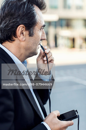 Side view of businessman communicating through headphones using mobile phone on street Stock Photo - Premium Royalty-Free, Image code: 698-07944669