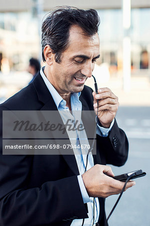 Businessman communicating through headphones while using mobile phone on street Stock Photo - Premium Royalty-Free, Image code: 698-07944670