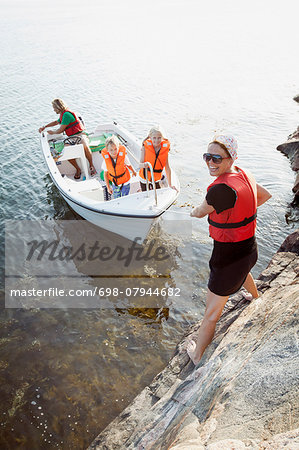 Portrait of happy woman pulling family in boat Stock Photo - Premium Royalty-Free, Image code: 698-07944682