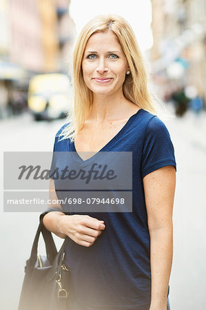 Portrait of smiling mid adult woman standing on street in city Stock Photo - Premium Royalty-Free, Image code: 698-07944698