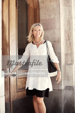 Portrait of happy woman opening door Stock Photo - Premium Royalty-Free, Image code: 698-07944749