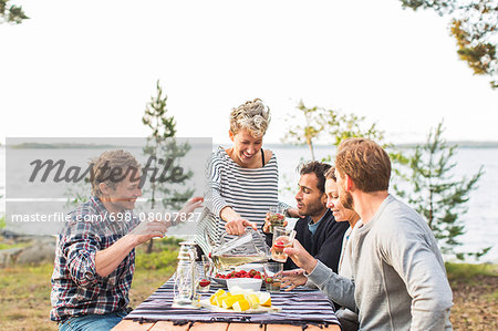 Happy woman serving beer to friends during lunch at lakeshore Stock Photo - Premium Royalty-Free, Image code: 698-08007827
