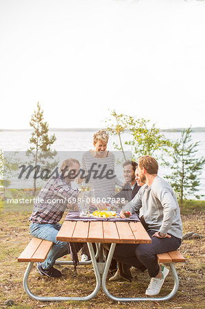 Happy friends having lunch at lakeshore Stock Photo - Premium Royalty-Free, Image code: 698-08007828