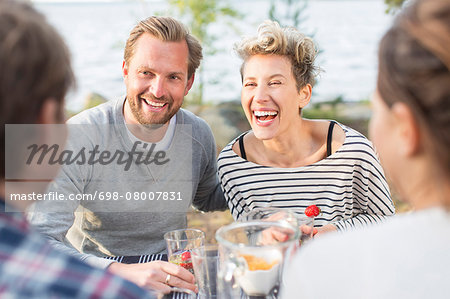 Happy friends enjoying during lunch at picnic table Stock Photo - Premium Royalty-Free, Image code: 698-08007831
