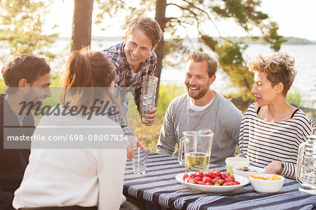 Group of friends enjoying while having lunch at lakeshore Stock Photo - Premium Royalty-Free, Image code: 698-08007834