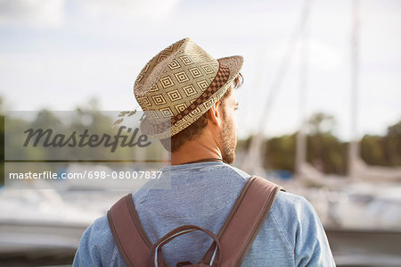 Rear view of man wearing hat and backpack at harbor