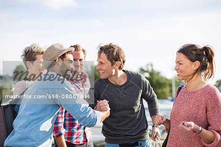 Happy friends greeting each other against sky Stock Photo - Premium Royalty-Free, Image code: 698-08007844
