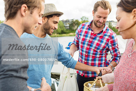 Happy friends with picnic basket outdoors Stock Photo - Premium Royalty-Free, Image code: 698-08007855
