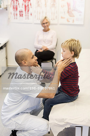 Senior woman looking at doctor and grandson touching each others throat at clinic Stock Photo - Premium Royalty-Free, Image code: 698-08007861
