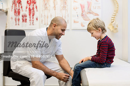 Male doctor checking knee reflexes of boy at orthopedic clinic Stock Photo - Premium Royalty-Free, Image code: 698-08007871