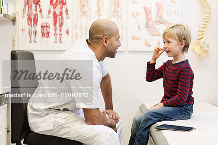Male orthopedic doctor talking to boy sitting on examination table in clinic Stock Photo - Premium Royalty-Free, Image code: 698-08007872