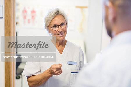 Senior doctor talking to man at orthopedic clinic Stock Photo - Premium Royalty-Free, Image code: 698-08007884