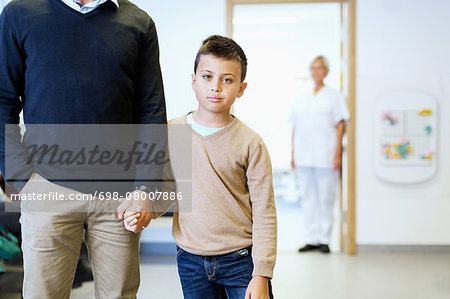 Portrait of boy holding father's hand with nurse in background at orthopedic clinic Stock Photo - Premium Royalty-Free, Image code: 698-08007886
