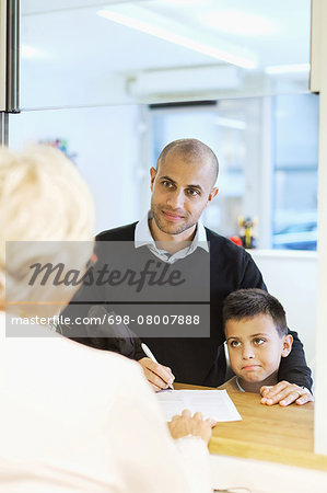 Father and son looking at receptionist while filling forms in orthopedic clinic Stock Photo - Premium Royalty-Free, Image code: 698-08007888